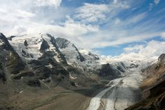 European mountain scenery. Austrian mountain range and glacier with fluffy white clouds stock images