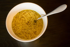 European noodle soup. A white bowl with European noodle soup with spoon on a brown wooden table Stock Photography