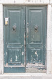 European old doors that have survived the test of time. Dull worn out green door with old fashioned door knockers Stock Images