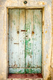 European old doors that have survived the test of time. Faded green door with a red step Royalty Free Stock Photo