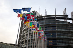 The European Parliament building in Strasbourg, France with flags waving on a evening stock photo