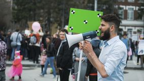 European people at demonstration. Man with a banner screaming into a mouthpiece. Angry adult young man with a banner in hands go and shouts loudspeaker rally