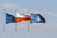 European, Polish and NATO flags. Warsaw, Poland. April 2019.   The flags of Poland, Europe and NATO waving on a blue sky stock photo
