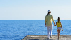 European pregnant mom and her little daughter are walking on breakwater to the blue sea under clear sky holding hands of each othe Royalty Free Stock Photo