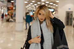 European pretty fashionable young blond woman in an elegant gray coat with a warm vintage scarf with a fashionable leather bag royalty free stock photo