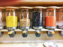 Cylindrical Clear Bulk Grains and Beans Dispenser. A European quality health food bulk foods section with a variety of grains and royalty free stock images