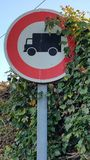 European road signs. Round road sign with vegetation growing over indicating no entry for trucks Royalty Free Stock Image