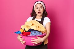 European slender housewife holds basin full of dirty clothes, stands with widely open mouth, impressed by washing process, wearing. White t shirt and brown stock photos