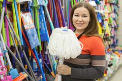 European woman buying mop in hypermarket store, looking at camera Royalty Free Stock Photo