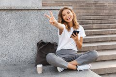 European smiling woman sitting on street stairs with legs crossed on summer day, and showing peace sign with mobile phone in hand. European smiling woman sitting royalty free stock image