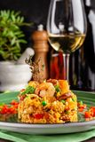 European Spanish cuisine. Paella with shrimps, chicken and coblas chorizo. White wine on the table. Closeup background image. Beautiful serving dishes in the royalty free stock photos