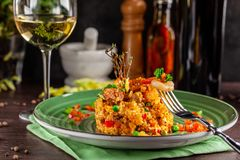 European Spanish cuisine. Paella with shrimps, chicken and coblas chorizo. White wine on the table. Closeup background image. Beautiful serving dishes in the royalty free stock photo