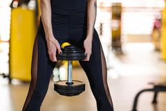 Sportswoman holds a dumbbell in the gym. Close-up. European sportswoman, dressed in a black tight-fitting sports suit, holds a heavy black dumbbell in the gym Royalty Free Stock Photo