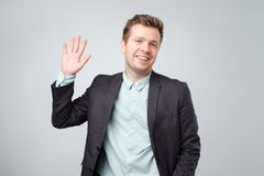 European student waives hand in hello gesture while smiling cheerfully isolated over white background. stock images