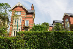 European-style houses behind verdant hedge in sunny autumn Royalty Free Stock Photography