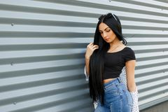 European stylish young hipster woman brunette with long luxurious hair in a trendy black top in a jacket in vintage jeans royalty free stock photos