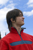 European teens man in red. Pretty  European teen boy in red sport pullover are looking up to blue sky Royalty Free Stock Photo