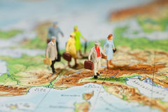 European Tourism And Travel. A group of miniature model tourists with luggage on a map of Europe, shallow DOF Royalty Free Stock Images