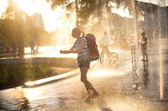 European tourist with a back pack in Tirana,. European tourist  with back pack washing hands in fountain water in Tirana city center square. water splashes in Royalty Free Stock Images