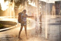 European tourist with back pack. Water splashes in sunset. European tourist washing hands in fountain water in Tirana city center square. water splashes in Royalty Free Stock Images