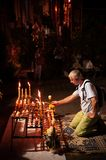 European tourist lit candles in Thai Buddhist temple stock photography