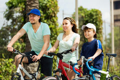 European tourists with son riding bicycles in park Stock Images