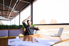 Translator sorting papers and closing laptop lid. European translator sorting papers and closing laptop lid at cafe. Young persistent man dressed in black shirt Royalty Free Stock Images