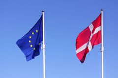 European Union EU and danish flag for Denmark on a pole waving in the wind with a blue sky on a sunny day. As background Royalty Free Stock Images