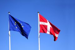 European Union EU and danish flag for Denmark on a pole waving in the wind with a blue sky on a sunny day. As background Royalty Free Stock Photo