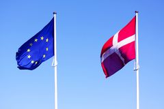 European Union EU and danish flag for Denmark on a pole waving in the wind with a blue sky on a sunny day. As background Stock Images