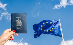 Canadian passport and EU flag - travel theme stock photography