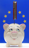 European Union financial crisis. European Union flag in front with a knife stabbed pig bank Stock Images
