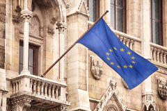 European Union Flag. The twelve yellow star flag of Europe (also known as Flag of the European Union and of the Council of Europe) waving from the facade of an stock photos