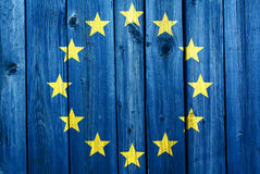 European Union flag in the background of an old wooden texture. European Union flag in the background of an old cracked wooden texture Stock Photos