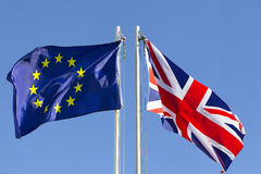 European Union flag and flag of UK on flagpole. In front of blue sky royalty free stock photo