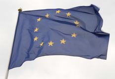 European Union flag flying in front of bright blue sky.  royalty free stock photography