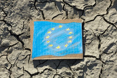 European Union flag painted on paper lying on cracked earth Stock Photos