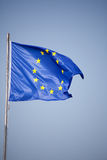 European Union flag in the wind. EU Flag with twelve stars on blue background Royalty Free Stock Images