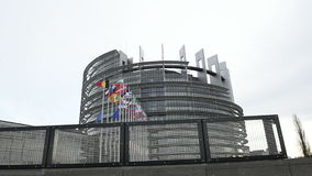 European Union Flags and France flag flies at half-mast seen through fence stock video footage