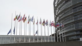 European Union Flags and France flag flies at half-mast seen through fence stock video