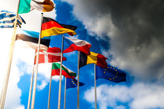 European union flags. Flags of members of european union between sunlight and rain Royalty Free Stock Photo