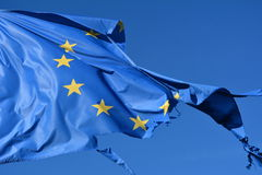 The european union twelve star flag torn and with knots in the wind on blue sky royalty free stock photo