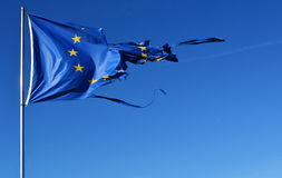The european union twelve star flag torn and with knots in the wind on blue sky stock photo