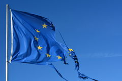 The european union twelve star flag torn and with knots in the wind on blue sky stock image