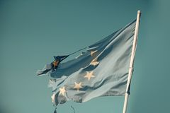 European union twelve star flag torn and with knots in wind on blue sky background. Flag is torn off at side, symbol of. Problems, decay, disintegration Stock Photos