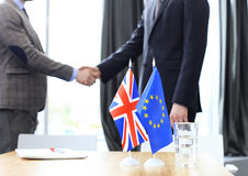 European Union and United Kingdom leaders shaking hands on a deal agreement. Brexit. Royalty Free Stock Images