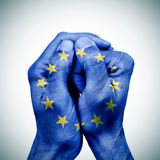 The european union in your hands. The clasped hands of a young man patterned with the flag of the european union royalty free stock photos