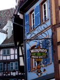 European Village Pub Sign. With Murphy`s Irish Stout in historical downtown Colmar Germany Royalty Free Stock Images