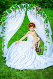 European wedding. Beautiful bride with chaming red hair sitting under the wedding arch. Wedding dress and accessories. Wedding decoration Stock Photos