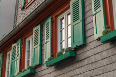 European windows with green wooden shutters in old house. Outdoo Royalty Free Stock Photography